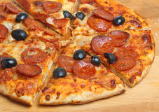 Pepperoni Pizza with Olives. Freshly baked and sliced pepperoni pizza with black olives Royalty Free Stock Photo
