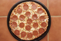 Pepperoni Pizza Pan. Delicious pepperoni and cheese pizza in a pan on the kitchen countertop Stock Photography