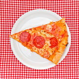 Pepperoni pizza slice on white plate Stock Photography