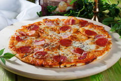 Pepperoni pizza in a still life wooden table top Royalty Free Stock Images