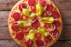 Pepperoni pizza on a table close-up vertical top view , rustic Stock Photo