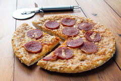 Pepperoni Pizza on a Wooden Board. Pepperoni and cheese pizza on a wooden board with a pizza cutter Stock Photos