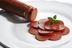 Pepperoni. On white plate wooden background royalty free stock photo