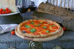 Pepperonipizza mit Rotwein stockbilder