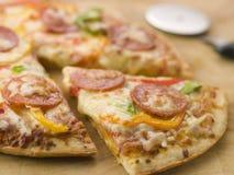 Pepperonis und Pfeffer-Pizza mit einem Pizza-Scherblock lizenzfreies stockfoto
