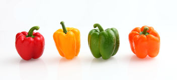 Peppers. In many colors green, yellow, orange and red all in white background Royalty Free Stock Images