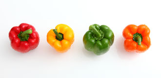 Peppers. In many colors green, yellow, orange and red all in white background Stock Images