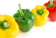 Peppers. A few peppers of different colours in line on the white background stock photography