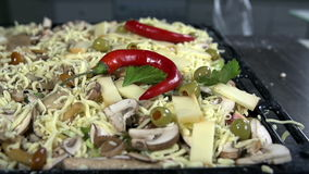 Peppers are added to the juicy pizza. Adding various pizza ingredients all over the dough stock video