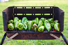 Peppers on barbecue. Grren peppers baking on a barbecue outside on the grass Stock Photo