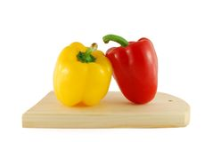 Peppers on the board. A red and yellow peppers on the board stock photo