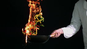 Peppers burning in a pan with big flame in slow motion Royalty Free Stock Images