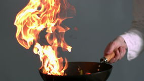 Peppers burning in a pan with big flame in slowmotion Stock Image