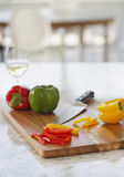 Peppers On Chopping Board In Kitchen Royalty Free Stock Photos
