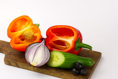 Peppers, cucumber, olives and onion on. Two peppers, cucumber, olives and onion on the wooden breadboard Royalty Free Stock Image