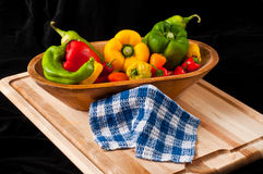 Peppers on Cutting Board. Still life of assorted green, red and yellow peppers in a wooden bowl on a cutting board with a check kitchen towel Royalty Free Stock Photo