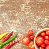 Peppers of different colors and red tomatoes on the table stock image