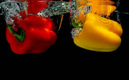 Peppers falling into water. Yellow and red peppers falling into water royalty free stock image