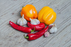 Peppers and garlic. Still life of chili peppers,paprika and garlic on wooden surface Royalty Free Stock Photography