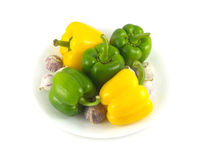 Peppers and garlic on white plate isolated close up Royalty Free Stock Photos