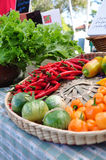 Peppers and greens at the farmers market. Spicy cayennepeppers, habaneros, yellow peppers, eggplant, and greens on display at the farmers market Royalty Free Stock Images