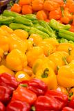 Peppers at the Grocer's. Piles of red, yellow, and orange peppers at the local grocery store. Focus on the yellow peppers Royalty Free Stock Photos