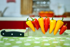 Peppers on a knife Stock Photography