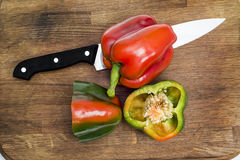 Peppers with knife. On a wooden board Stock Photography