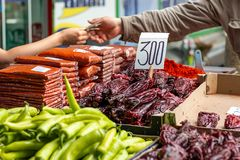 Peppers on the marketplace. Different types of green and red peppers on the marketplace in Belgrade. Blurred background of seller and customer hands paying cash royalty free stock images