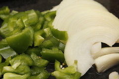 Peppers and onions. Chopped green peppers and white onions on marble chopping board Stock Photos