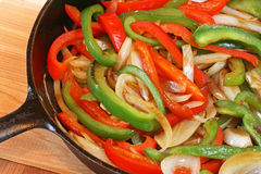 Peppers and onions in black cast iron skillet. Red and green bell peppers and onions sauteeing in black cast iron skillet Stock Image