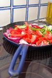 Peppers and onions cooking in a pan. Red and green peppers with red onion cooking in a blue pan on an electric hob with oil and tiles in background Stock Photos