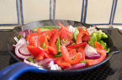 Peppers and onions cooking in a pan. Red and green peppers with red onion cooking in a blue pan on an electric hob with tiles in background Royalty Free Stock Photos