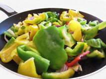 Peppers and onions in the cooking pan on white background Stock Image