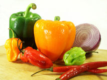 Peppers in a pile on a cutting board Royalty Free Stock Images