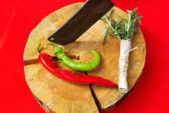 Peppers, rosemary and knife on the wooden cutting board. Stock Photos
