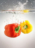 Peppers splashing in water Royalty Free Stock Image