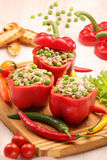 Peppers stuffed with meat rice and vegetables on cutting board Stock Photo