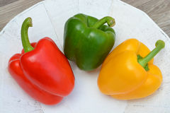 Peppers in three colors on a white natural plate Royalty Free Stock Photos