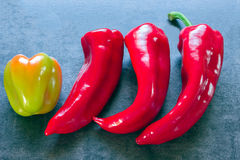 Peppers - three identical and one different in color and shape Stock Image