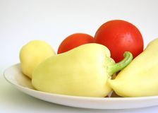Peppers and tomatoes. Yellow peppers and tomatoes on a plate stock photography