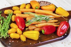 Peppers, tomatoes, carrots, thyme, basil on a table Stock Photos
