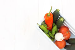Peppers, tomatoes, cucumbers and onions stuffed into a wooden box Stock Photo