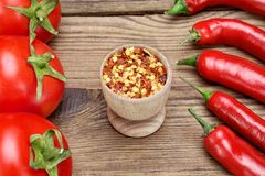 Peppers, Tomatoes and Milled Chili Peppers Flakes On Wooden Boar Stock Photos