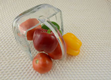 Peppers and tomatoes in overturned glass basket Stock Image