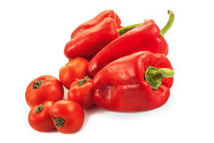 Peppers and tomatoes. Red peppers and tomatoes on white background Royalty Free Stock Images