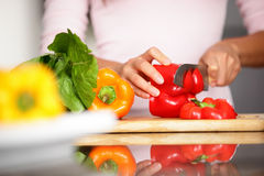 Peppers - woman cutting red pepper Stock Image