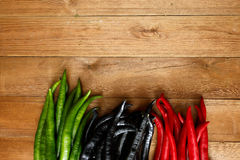 Peppers. On wood background Royalty Free Stock Photos