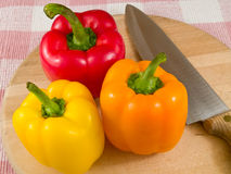 Peppers on a Wooden Cutting Board with Knife Royalty Free Stock Images