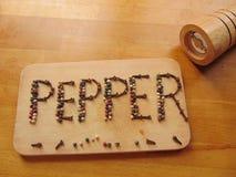 Peppra skriftligt på skärbräda, medan peppermill ligger bredvid den Royaltyfria Foton